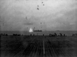 Japanese aircraft exploding near the stern of USS Corregidor, off Saipan, Mariana Islands, 17 Jun 1944; seen from the flight deck of USS Coral Sea