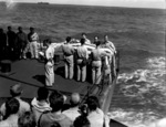 US Navy Chaplain W. M. Dunn conducting funeral service of Lieutenant (jg) Eugene Bradshaw aboard USS Coral Sea in the Pacific Ocean during the Mariana Islands campaign, 19 Jun 1944