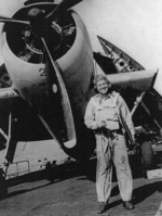 Lieutenant R. S. Evarts posing with a TBF Avenger aircraft aboard USS Coral Sea, 30 Oct 1943