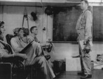 Lieutenant Commander J. J. Lynch conducting a pre-flight briefing aboard USS Coral Sea, 30 Oct 1943