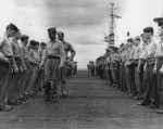 Ensign Richard Hansen (with Division Chief Kenneth Firestone) inspecting sailors aboard USS Anzio, 28 Apr 1945