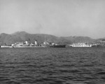 HMS Belfast in the channel at Busan, Korea, 2 Apr 1952; note hospital ship USS Consolation