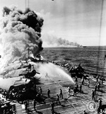Firefighters of Belleau Wood fighting flames caused by a special attack aircraft, in the Philippine Islands, 30 Oct 1944; note TBM Avenger aircraft on flight deck and Franklin burning in distance. Photo 1 of 2