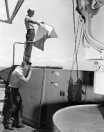 US Navy Signalman 2nd Class Kenneth Mitchell of battleship Colorado sending a message with semaphore flags, 29 Oct 1943; Signalman 3rd Class John Wilson on telescope