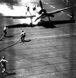 Firefighters extinguishing a burning Hellcat fighter on Cowpens, 24 Nov 1943