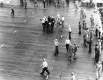 Wounded by aircraft gunfire, Aviation Ordnanceman Second Class Clifton R. Bassett of VB-3 was carried down the flight deck of Enterprise, 4 Jun 1942, photo 1 of 2
