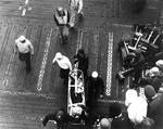 Wounded by aircraft gunfire, Aviation Ordnanceman Second Class Clifton R. Bassett of VB-3 was carried down the flight deck of Enterprise, 4 Jun 1942, photo 2 of 2