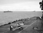 Grumman Martlet of 888 Squadron of British Fleet Air Arm taxiing on HMS Formidable after landing, circa 24 Apr-10 May 1942; HMS Warspite and AMC Alaunia in background