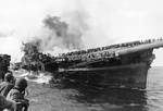 Franklin listing and afire after being hit by two bombs, off Japan, 19 Mar 1945; photograph taken from cruiser Santa Fe