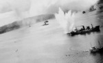 A bomb exploding off port quarter of a Japanese cargo ship in Simpson Harbor, Rabaul, New Britain, 2 Nov 1943; note Haguro in center distance and USAAF 3rd Bomb Group B-25 bomber in lower left; photo 1 of 2