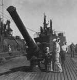 US Navy personnel inspecting a deck gun aboard Japanese submarine I-400, circa late 1945 or early 1946
