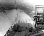 Battleship Indiana taking water over the bow while sailing through a typhoon in the Okinawa, Japan area, circa 5 Jun 1945