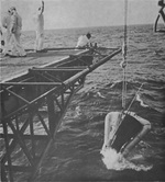 Gemini 3 spacecraft being hoisted aboard USS Intrepid during recovery, in the Atlantic Ocean north of the Dominican Republic, 23 Mar 1965, photo 2 of 2