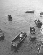 Wounded personnel being loaded from USS Intrepid into waiting LCVP landing craft, probably at Ulithi, Caroline Islands, 1944, photo 1 of 2