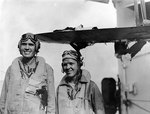 US Navy aviators Ensign William C. Orr and Aviation Radioman 3rd Class Thomas D. Everett of cruiser Louisville posed by their damaged SOC Seagull aircraft, Feb 1945