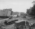 Six US Navy LSTs loading men and equipment during a practice landing near Lae, New Guinea, 10 Apr 1944; note M4 Sherman tank, Dodge Weapons Carrier, GMC CCKW 2 1/2-ton 6x6 trucks