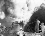 Men watched as firefighters battled flames on LST-480, 22 May 1944; the explosion took place on the previous day