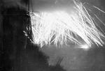 Tracer fire from Allied warships lighting up the sky off Ouistreham, France, 10 Jun 1944; photo taken from HMS Mauritius, seen in foreground