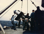 Crewmen hoisting one of USS Miami