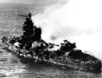 Mikuma burning, with midships structure shattered and torpedo dangling from tube, 6 Jun 1942