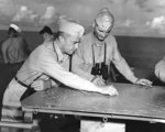 Rear Admiral Aaron Merrill working with Captain W. D. Brown aboard USS Montpelier, Solomon Islands area, 23 Dec 1943