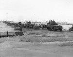 US Army vehicles came ashore on one of the floating causeways of the Mulberry artificial harbor off Omaha Beach, Normandy, 16 Jun 1944