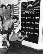 Men of US Navy Submarine Squadron 5 keeping score of sinkings aboard USS Griffin, 7 Jan 1943; the squadron operated out of Brisbane, Australia