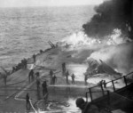 Following an attack from Japanese special attack aircraft, fires grew in the forward hangar deck of USS Saratoga off Iwo Jima, 21 Feb 1945. The fires increased greatly before they could be controlled. Photo 2 of 3