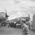 Flight deck crews of USS Saratoga spotting SBD-5 Dauntless dive bombers of VB-12 squadron, Oct 1943