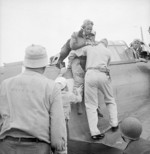SBD Dauntless crewman Alva Parker, having suffered neck and shoulder shrapnel wounds over Rabaul, New Britain, being helped from the aircraft after landing on USS Saratoga, 5 Nov 1943