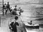 Crew of USS Tang taking aboard airmen of downed OS2U Kingfisher aircraft from USS North Carolina, off Truk, Caroline Islands, 1 May 1944
