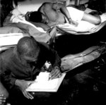 African-American US Navy sailors STM1/c Thomas L. Crenshaw (looking at photos) and his bunkmate (writing letter) aboard USS Ticonderoga, off Philippine Islands, 4 Nov 1944