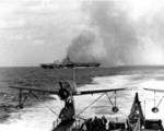 Carrier Ticonderoga burning after being struck by special attack aircraft off Taiwan, 21 Jan 1945; note light cruiser Miami
