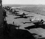 F6F Hellcat aircraft preparing for takeoff from Ticonderoga for strikes in Manila Bay, Philippine Islands, 5 or 6 Nov 1944; note two leading planes were F6F-5N nightfighters with wing-mounted radar