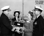 RAdm Mahlon Tisdale presenting champagne bottle to Mrs Davenport to christen Trepang, Mare Island Naval Shipyard, California, United States, 23 Mar 1944; Mrs Garvey and Cmdr Roy Davenport also present