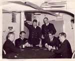 Lieutenant Harold Kelly (standing with pipe) and other officers playing cards aboard USS Wasp, date unknown