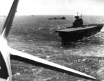 USS Yorktown seen from a TBD-1 aircraft, Pacific Ocean, Apr 1942; note F4F-3 Wildcat fighter preparing for takeoff, and fleet oiler USS Guadaloupe, a destroyer, and a cruiser just beyond