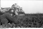German soldier with binoculars in the Flanders region of France or Belgium, Jun 1944; note PzKpfw 35 S 739(f) medium tank in background