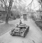 Covenanter tanks and towed artillery passing through a village during Exercise Spartan, Britain, 6 Mar 1943