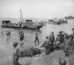 African-American soldiers of a port battalion of the US 5th Army unloading supplies at the beach at Salerno, Italy, 18 Sep 1943; note DUKW in center and fresh water cans marked with