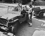 US Army Captain Thomas Ryan checking in civilian photo technicians at a checkpoint in Potsdam, Germany, 14 Jul 1945; note Willys MB jeep; the military policeman was Corporal Charles Christie
