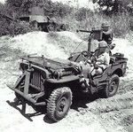 Jeep mounted with a Browning M1919 machine gun, somewhere in the Pacific, 1943-1945; note hulk of Japanese Type 95 Ha-Go light tank