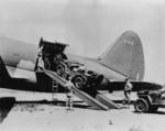 A Jeep being loaded into the sizeable fuselage of a C-46 Commando cargo plane, while another waited to be driven up the ramp, Mar 1942