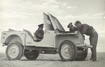 Members of the No. 3 Squadron RAAF checking under the hood of a Bantam BRC 40 Jeep in Libya