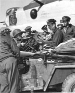 US armored division troops letting an 8th Air Force officer try a German MP 40 machine pistol, England, United Kingdom, 1943-1945; note Jeep vehicle, B-24H bomber, and M1 Garand rifle