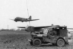 C-47 Skytrain with hook lowered preparing to snatch CG-4 glider as the Control Team stands by in a GPW/MB Jeep, date unknown
