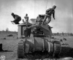 Corporal Larry Corletti, Private Murril Chapman, and Private Louis Robles practicing abandoning a M3 medium tank at Camp Polk, Louisiana, United States, 12 Feb 1943