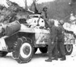 M8 armored car of US 11th Armored Division with men of US 84th Infantry Division in Noville, Belgium, 16 Jan 1945