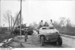 German SdKfz. 251 halftrack vehicle on a road, Russia, 21 Mar 1944, photo 1 of 2; note destroyed Russian (American-made) M4 Sherman medium tank in background