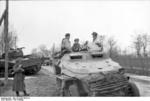 German SdKfz. 251 halftrack vehicle on a road, Russia, 21 Mar 1944, photo 2 of 2; note destroyed Russian (American-made) M4 Sherman medium tank in background